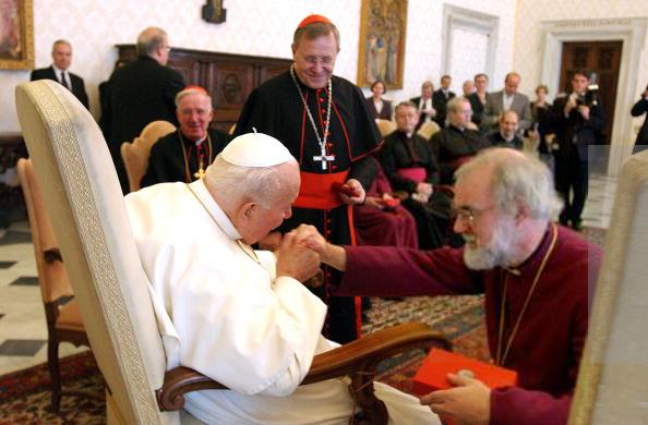 Jean-Paul II embrassant l'anneau de Rowan Williams, le chef de la secte anglicane, auquel il conféra aussi la croix pectorale, bien que Williams ne soit qu'un laïc.