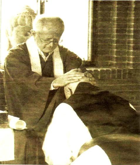 Le « prêtre » trappiste, P. Kevin Hunt, à genoux tandis qu'il est institué professeur de Zen par le  « jésuite » P. Robert Kennedy